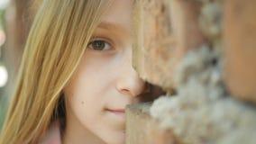 Fronte triste del bambino che gioca nascondino, ragazza spaventata dietro le pareti che sorride in camera immagini stock libere da diritti