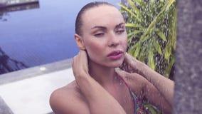 Fronte vicino su della donna bionda sexy in bikini che prende all'aperto doccia alla piscina circondata con il giardino tropicale archivi video