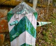 A fronteira velha listrou branco com uma barreira verde na floresta imagens de stock royalty free