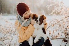Frontera blanco y negro linda mullida adorable colly que es entrenada y que acaricia a la muchacha en un parque luces y arbustos  fotos de archivo