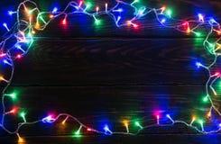 Frontera brillante de la guirnalda en fondo de madera Imagen de archivo libre de regalías