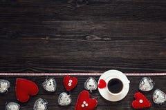 Frontera de corazones de la tarjeta del día de San Valentín y taza de café en el woode oscuro Fotografía de archivo