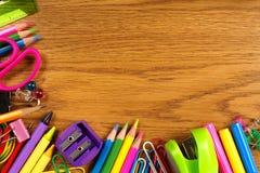 Frontera de la esquina de las fuentes de escuela en el escritorio de madera Foto de archivo libre de regalías