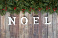 Frontera de la Navidad con el abeto, las bayas rojas y Noel Letters Imágenes de archivo libres de regalías