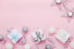 Frontera de la Navidad con las cajas de regalo, las bolas, la decoración y las lentejuelas en la opinión de sobremesa rosada Ende foto de archivo libre de regalías