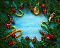Frontera de la Navidad con las ramas de árbol de abeto, conos, decoros de la Navidad Imagenes de archivo