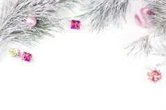 Frontera de la Navidad con las ramas del abeto, las cajas de regalo, las bolas de la Navidad y los ornamentos en el fondo blanco Imagenes de archivo