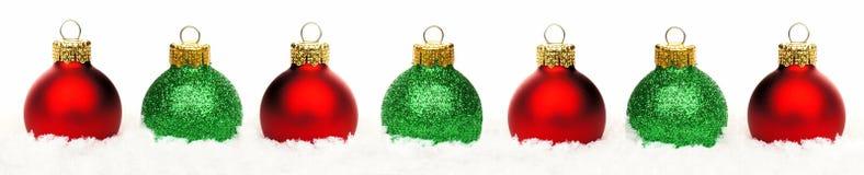 Frontera de la Navidad de chucherías rojas y verdes en la nieve aislada Fotos de archivo libres de regalías