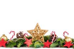 Frontera de la Navidad - ramas de árbol con las bolas de oro, el caramelo y la estrella grande aislados en blanco Foto de archivo