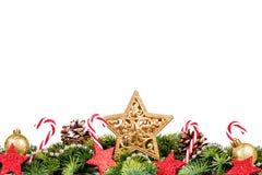 Frontera de la Navidad - ramas de árbol con las bolas de oro, el caramelo y la estrella grande aislados en blanco Imagen de archivo libre de regalías