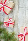 Frontera de las cajas de regalo de la Navidad y rama de árbol de abeto en la tabla de madera Foto de archivo