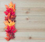 Frontera de las hojas de otoño en un fondo de madera imagenes de archivo