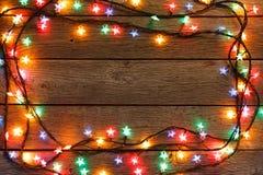 Frontera de las luces de la Navidad en el fondo de madera Imagenes de archivo