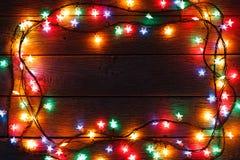 Frontera de las luces de la Navidad en el fondo de madera Fotografía de archivo libre de regalías