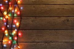 Frontera de las luces de la Navidad en el fondo de madera Imagen de archivo
