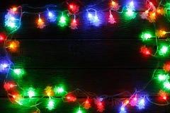 Frontera de las luces de la Navidad en fondo de madera negro Fotos de archivo libres de regalías