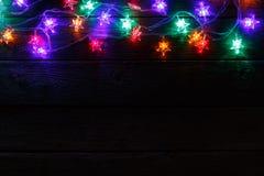 Frontera de las luces de la Navidad en fondo de madera negro Imágenes de archivo libres de regalías
