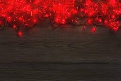 Frontera de las luces rojas de la Navidad en fondo de madera gris Imagen de archivo
