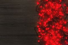 Frontera de las luces rojas de la Navidad en fondo de madera gris Fotografía de archivo