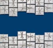 Frontera de los regalos brillantes de plata en fondo azul ` S del Año Nuevo y decoración de la Navidad Fotografía de archivo libre de regalías
