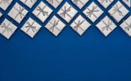 Frontera de los regalos brillantes de plata en fondo azul ` S del Año Nuevo y decoraciones de la Navidad Fotografía de archivo libre de regalías