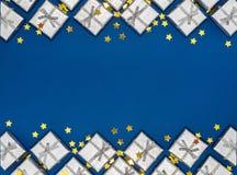 Frontera de los regalos brillantes de plata y de las estrellas de oro en fondo azul Decoraciones de la Navidad Imagen de archivo