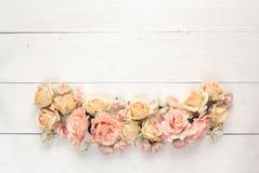 Frontera de rosas en un fondo de madera blanco con el espacio vacío FO Foto de archivo
