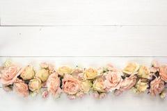 Frontera de rosas en un fondo de madera blanco con el espacio vacío FO Imagen de archivo