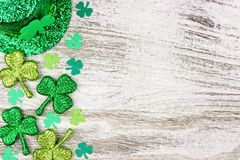 Frontera de tréboles, sombrero del lado del día del St Patricks del duende sobre la madera blanca foto de archivo libre de regalías