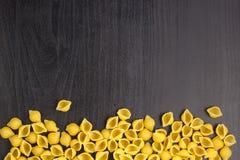 Frontera de una pila de cáscaras de la goma del conchiglie en fondo negro con el copyspace foto de archivo libre de regalías