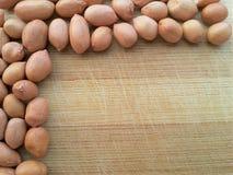 Frontera del cacahuete en fondo de madera Foto de archivo libre de regalías
