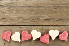 Frontera del caramelo del día de tarjetas del día de San Valentín en el fondo de madera Fotografía de archivo libre de regalías