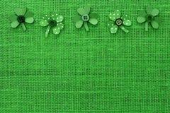 Frontera del día del St Patricks de los tréboles de papel en la arpillera verde Fotos de archivo libres de regalías