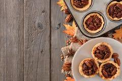 Frontera del lado de la escena de la hornada del otoño con las tartas de la pacana sobre la madera Imágenes de archivo libres de regalías