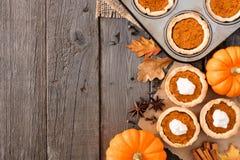 Frontera del lado de la hornada del otoño con las tartas de la calabaza sobre la madera Fotografía de archivo