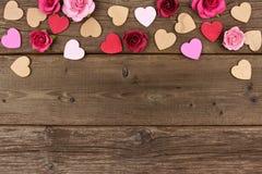 Frontera del top del día de tarjetas del día de San Valentín de corazones y de rosas contra la madera rústica imagen de archivo libre de regalías