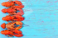 Frontera roja colorida de la langosta en la madera azul Fotos de archivo libres de regalías
