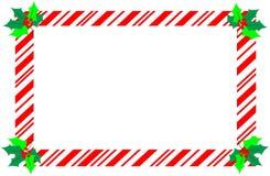Frontera roja del bastón de caramelo de la Navidad con acebo Fotos de archivo libres de regalías