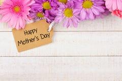 Frontera superior de flores con la etiqueta del regalo del día de madres contra la madera blanca Foto de archivo libre de regalías