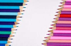 Frontière/bord des crayons colorés avec bleu/pourpre sur un latéral et rose/pourpre sur l'opposé avec l'espace blanc dans l'i images libres de droits