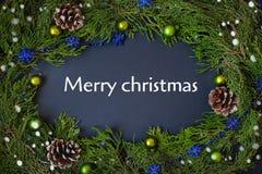 Frontière, cadre des branches d'arbre de Noël avec des cônes de pin et baies bleues inscription joyeuse au centre du Photographie stock