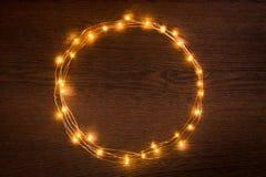 Frontière circulaire de guirlande de lumières de Noël au-dessus de fond en bois foncé Configuration plate, l'espace de copie photos stock