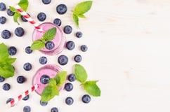 Frontière décorative du smoothie violet de fruit de myrtille dans des pots en verre avec la paille, feuilles en bon état, baies,  Images stock
