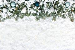 Frontière d'arbre de sapin de Noël avec des babioles d'arbre de Noël sur la neige Photographie stock