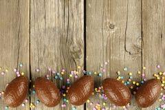 Frontière d'oeuf de pâques de chocolat sur le bois photo stock