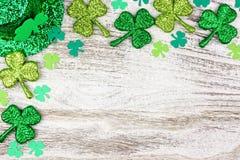 Frontière de coin de jour de St Patricks des oxalidex petite oseille, chapeau de lutin au-dessus du bois blanc photo stock