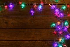 Frontière de lumières de Noël sur le fond en bois Photographie stock libre de droits