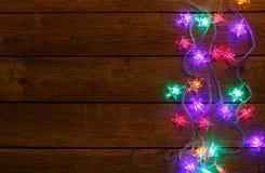 Frontière de lumières de Noël sur le fond en bois Photographie stock