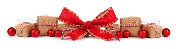 Frontière de Noël avec les boîte-cadeau bruns et blancs et l'arc rouge d'isolement Photographie stock libre de droits