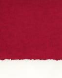 Frontière de papier déchiquetée sur le rouge Image stock